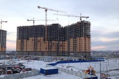 Processen av att bygga stor mång--våning en bostads- byggnad i vintern Arbetet av konstruktionskranar Halva byggt hus arkivfoton