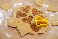 Processen av att göra ljust rödbrun kakor i form av en hjärta, pepparkaka arkivbild