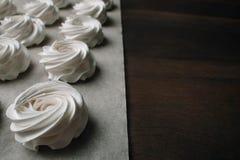 Processen av att göra marshmallowen Stäng sig upp händer av kocken med konfektpåsekräm till pergamentpapper på bakelse shoppar royaltyfria foton