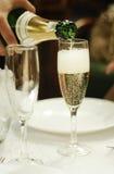 Processen av att hälla champagne in i ett exponeringsglas royaltyfri fotografi
