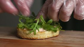 Processen av att laga mat den stora hamburgaren är en yrkesmässig kock, närbild Sätter lökar på en rulle stock video
