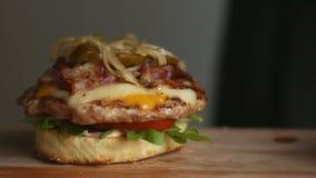 Processen av att laga mat den stora hamburgaren är en yrkesmässig kock, närbild Sätter små pastejer med ost på en bulle lager videofilmer