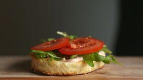 Processen av att laga mat den stora hamburgaren är en yrkesmässig kock, närbild Sätter tomater på en rulle arkivfilmer