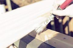 Processen av att måla en trälist utomhus Hem- renoveringbegrepp royaltyfria bilder