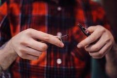 Processen av att serva den mekaniska vapeapparaten Förlagen byter ut tråd för att röka Ecig rapairing process Fotografering för Bildbyråer