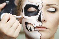 Processen av att skapa makeup för allhelgonaafton Arkivfoto