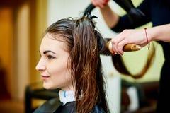 Processen av att torka håret av ett ungt royaltyfri bild