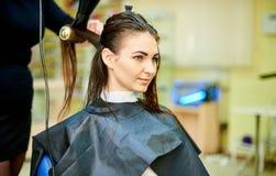 Processen av att torka håret av ett ungt royaltyfri foto