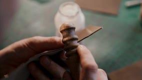 Processen av tillverkning en handgjord läderplånbok En hantverkare som maler ett stycke av läder Handgjort lädergods lager videofilmer