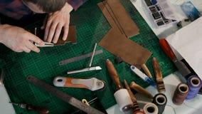 Processen av tillverkning en handgjord läderplånbok Hantverkaren klippte av ett stycke av läder Handgjort lädergods arkivfilmer