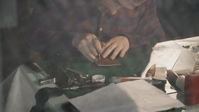 Processen av tillverkning en handgjord läderplånbok Hantverkarestansmaskinhålen för att exponera Handgjort lädergods lager videofilmer