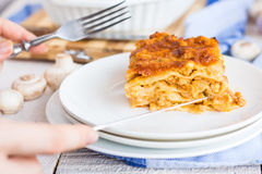 Processes eating mushroom lasagna, devices, hands Stock Image