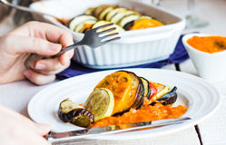 Processes food vegetable ratatouille with a fork and knife, hand Stock Photo