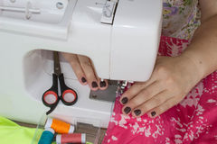 Processes of sewing on the sewing machine sew women`s hands sewing machine. Female tailor threading leather material on sewing ma Stock Photo