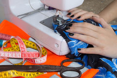 Processes of sewing on the sewing machine sew women`s hands sewing machine. Female tailor threading leather material on sewing ma Stock Images