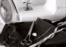 Processing bottom jeans. With the aim of shortening the trouser Stock Images