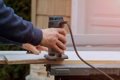 Processing carpenter with Electronic Plunge Router of wooden boards hand cutter close-up royalty free stock image