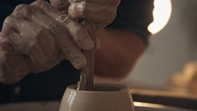 Processing clay ware and making dishes, process. Ceramics. Chamber atmosphere of the creative workshop: man works with a potter`s wheel, only hands. Processing stock footage