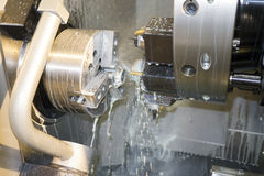 Processing detail on CNC lathe with coolant. Work zone of CNC machine Royalty Free Stock Photo