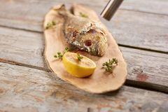 Processing dorado grill with torch burner. Barbecued dorado with with lemon on wooden board. Delicious dinner on table stock images