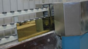 Processing of the edge of the glass with gold coating on the machine tool with program control. Factory for the. Production of windows. close-up stock footage