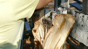 Processing of firewood. Worker splitting large trunk with a hydraulic ax,video clip stock video