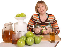 Processing of fruit. The young woman prepares for apple juice Stock Photography
