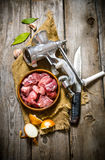 Processing of meat. Fresh raw meat in a onion with chopper, knife and spices on old fabric. On a wooden table. Top view Royalty Free Stock Photo