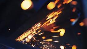 Processing of metal grinder with sparks. Craftsman sawing metal with disk grinder in workshop. Slow Motion. Flies of spark from hot metal stock footage