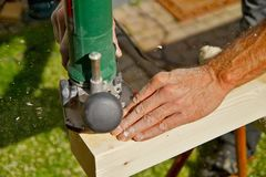 Processing of Natural Wooden beam with milling woodworking machine. male Hand of carpenter holds a carpentry tool. royalty free stock photos