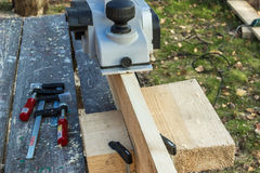 Processing wooden planks electric plane. Work electric planers, the board, without special hardware Stock Photos