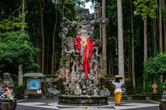 Procession av härliga Balinesekvinnor i traditionella dräkter - saronger som går till hinduisk ceremoni nära den stora demonmonum arkivbild