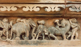 Procession of indian people, elephants on stone wall of Khajuraho temple, India. UNESCO Heritage site, Royalty Free Stock Image