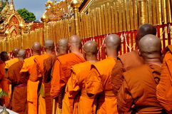 Chiang Mai,Thailand: Monks at Wat Doi Suthep. A procession of monks with shaven heads walking past the gilded gates at the base of the golden Chedi at Wat Doi Royalty Free Stock Photo