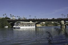 The procession passes over the Guadalquivir river on the Triana bridge in Seville. The Spanish world between fun and sacrality stock photo