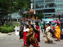 Procession during Thaipusam. Mostly barefooted, devotees walk along the hot road in the afternoon sun during the procession of Thaipusam, Festival of Light Royalty Free Stock Image