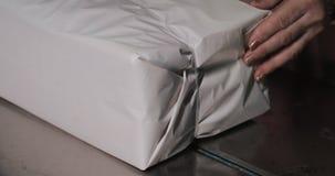 Processo d'imballaggio di un covone del giornale tenuto da una donna sulla vecchia fabbrica del giornale stock footage