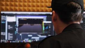 Processo da gravação da música no estúdio de gravação da casa Coordenador sadio que trabalha em misturar e em dominar a música co vídeos de arquivo