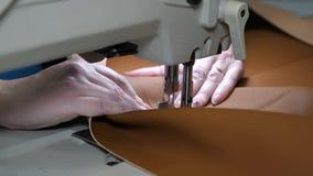 processo de costurar o couro artificial agulha da m?quina de costura no movimento uma costureira costura o couro preto em costura filme