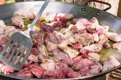 Processo de cozinhar a carne suculenta cortada de fritura da galinha e do coelho na grande bandeja lisa do paella Lanç com metal  Imagem de Stock