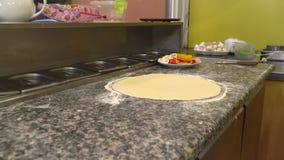 Processo de cozinhar a pizza com uma massa fina Há uma placa com pimentas desbastadas, tomates, recipientes de alimento do metal  filme