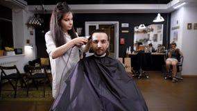Processo de fazer o corte de cabelo Front View Cliente masculino do moderno e barbeiro fêmea Ideia do interior da barbearia filme