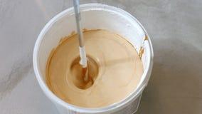Processo de misturar a pintura branca com um tinge da cor na cubeta imagem de stock