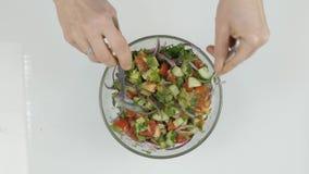 Processo de misturar a salada fresca com a colher e a forquilha Processo da preparação da salada Vista superior 4K filme