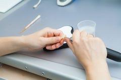 Processo de moer a maxila durante a produção O técnico dental processa os dentes artificiais com um micromotor fotografia de stock