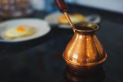 Processo de preparar um café da manhã clássico: ovos fritos em uma frigideira, um turco turco clássico para cozinhar o café em um Imagem de Stock