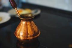 Processo de preparar um café da manhã clássico: ovos fritos em uma frigideira, um turco turco clássico para cozinhar o café em um Fotos de Stock Royalty Free