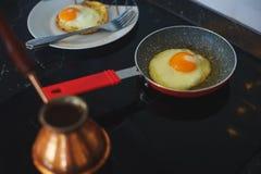 Processo de preparar um café da manhã clássico: ovos fritos em uma frigideira, um turco turco clássico para cozinhar o café em um Imagens de Stock