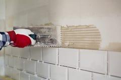 Processo de telhar as telhas na cozinha Melhoria home, com referência a imagem de stock royalty free