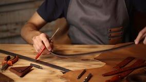 Processo de trabalho da correia de couro na oficina de couro Homem que guarda crafting a ferramenta e trabalhar Curtidor em velho filme